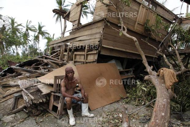 A man takes a break from salvaging reusable woods from his damaged house after super Typhoon Haiyan hit Tabogon town