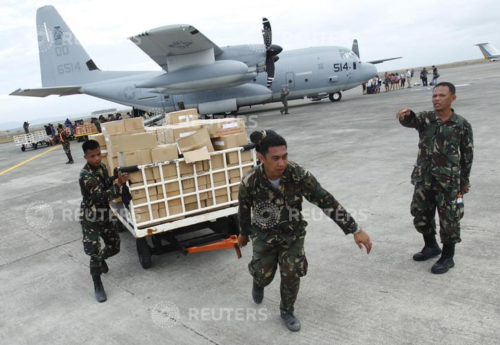 Military personnel deliver aid supplies at the destroyed airport after super typhoon Haiyan battered Tacloban City, in central Philippines