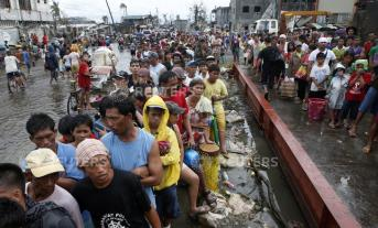 Typhoon victims queue for free rice at a businessman's warehouse in Tacloban city, which was battered by Typhoon Haiyan, in central Philippines