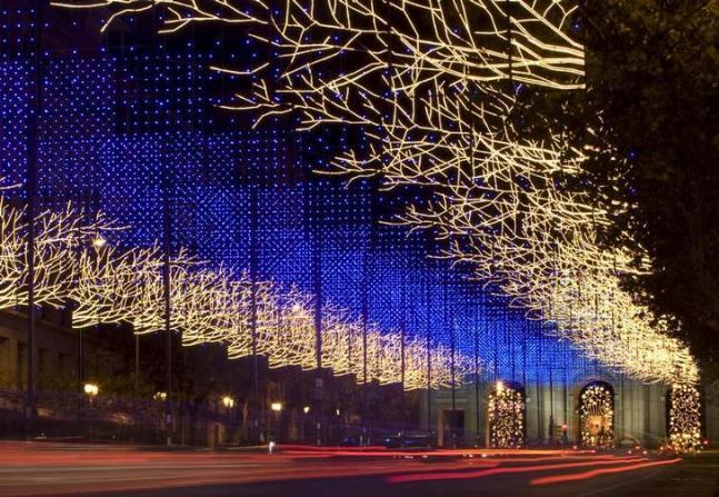 Traffic streams up Alcala street under Christmas lighting in central Madrid