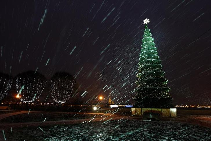 A lit Christmas tree is seen amidst snowfall in St. Petersburg