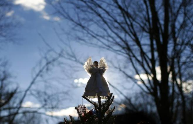 An angel sits atop a Christmas tree in a growing makeshift memorial for the victims of the December 14 shootings at the Sandy Hook Elementary School in Sandy Hook village in Newtown