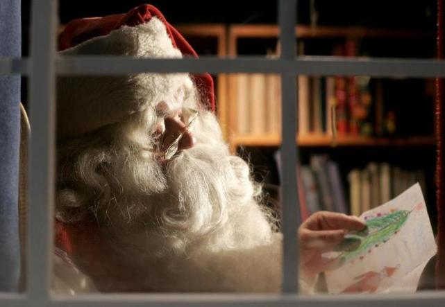 A man dressed as Santa Claus reads letters from children from around the world in his office at the Santa Claus' Village at the Arctic Circle near Rovaniemi