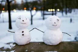 Pint-sized snowmen are seen on a railing at Central Park in New York