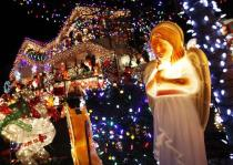 A figure of an angel is seen as part of a house decorated with Christmas lights in the borough of Queens in New York