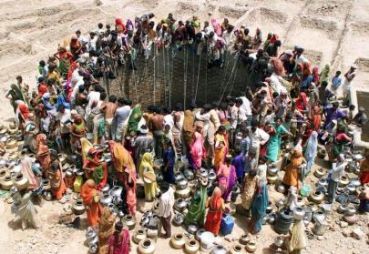 ATTENTION EDITORS - 14 OF 21 PICTURES TO MATCH PACKAGE 'WORLD POPULATION - SEVEN BILLION' - TO FIND ALL PICTURES SEARCH 'POPULATION-BABY/' People gather to get water from a huge well in the village of Natwarghad in the western Indian state of Gujarat, in this file picture taken June 1, 2003. The world's population will reach seven billion on 31 October 2011, according to projections by the United Nations, which says this global milestone presents both an opportunity and a challenge for the planet. While more people are living longer and healthier lives, says the U.N., gaps between rich and poor are widening and more people than ever are vulnerable to food insecurity and water shortages. REUTERS/Amit Dave/Files (INDIA DAY - Tags: HEALTH SOCIETY TPX IMAGES OF THE DAY)