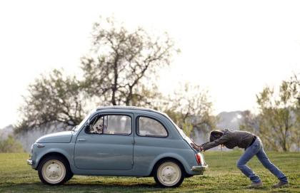 A woman pushes her Fiat 500 car as her dog sits inside, in a neighbourhood of Rome March 23, 2012. Picture taken March 23, 2012. REUTERS/Alessandro Bianchi (ITALY - Tags: ANIMALS SOCIETY TRANSPORT)