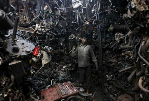 Abdul Samad, 13, carries a part of a used car engine inside an automobile workshop in Mumbai July 10, 2012. An Indian automobile industry body on Tuesday slightly lowered its car sales growth forecast for the year ending next March, as higher costs and slower economic expansion impinge on demand. REUTERS/Danish Siddiqui (INDIA - Tags: BUSINESS SOCIETY TRANSPORT)
