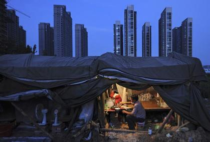 A labourer has his dinner under his shed at a construction site of a residential complex in Hefei, Anhui province, August 1, 2012. The average home price in China's 100 major cities edged up in July for the second straight month, reinforcing signs of a recovery in the property market even as the government seeks to spur broader economic growth, a private sector survey showed on Wednesday. Picture taken August 1, 2012. REUTERS/Stringer (CHINA - Tags: BUSINESS SOCIETY CONSTRUCTION REAL ESTATE TPX IMAGES OF THE DAY)