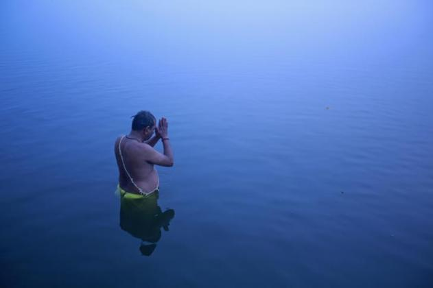 A Hindu devotee stands in the waters of river Ganges to offer prayers to Sun god at dawn in Varanasi, in the northern Indian state of Uttar Pradesh January 12, 2013. REUTERS/Danish Siddiqui (INDIA - Tags: SOCIETY RELIGION TPX IMAGES OF THE DAY)