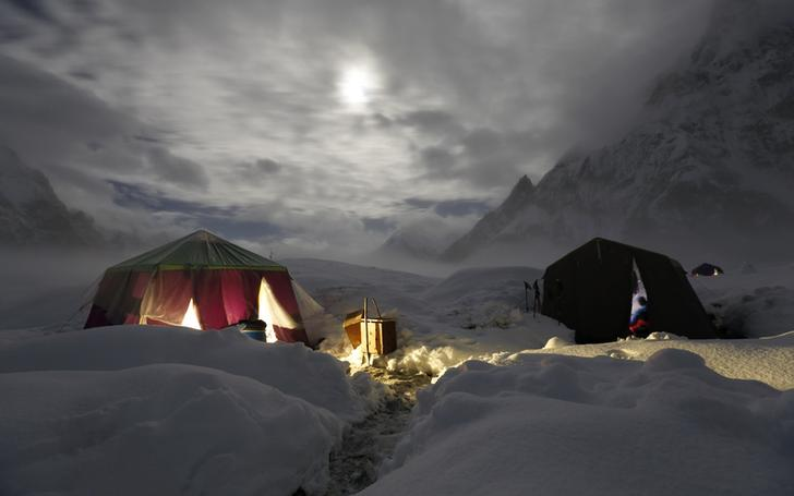 The moon illuminates the snow-covered Concordia, the confluence of the Baltoro and Godwin-Austen glaciers, near the world's second highest mountain the K2 (8,000 meters) in the Karakoram mountain range in Pakistan September 6, 2014. While other parts of Pakistan and northern India were flooded, Concordia in the Karakoram mountain range was covered with a seasonally unusual amount of snow. Geographically, Pakistan is a climbers paradise. It rivals Nepal for the number of peaks over 7,000 meters and is home to the world's second tallest mountain, K2, as well as four of the world's 14 summits higher than 8,000 meters. In more peaceful times, northern Pakistan's unspoilt beauty was a major tourist draw but the potentially lucrative industry has been blighted by years of violence. The number of expeditions has dwindled, wrecking communities dependant on climbing for income and starving Pakistan's suffering economy of much-needed dollars. Picture taken September 6, 2014. REUTERS/Wolfgang Rattay (PAKISTAN - Tags: ENVIRONMENT SOCIETY TPX IMAGES OF THE DAY TRAVEL) ATTENTION EDITORS - PICTURE 27 OF 32 FOR WIDER IMAGE STORY 'K2 - THE SAVAGE MOUNTAIN' SEARCH 'RATTAY K2' FOR ALL IMAGES