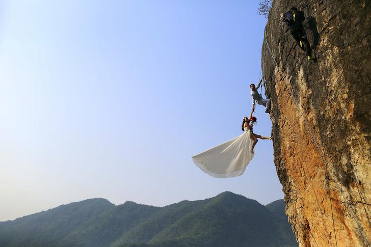 Zheng Feng, an amateur climber takes wedding pictures with his bride on a cliff in Jinhua, Zhejiang province, October 26, 2014. Picture taken October 26, 2014. REUTERS/China Daily (CHINA - Tags: SOCIETY TPX IMAGES OF THE DAY) CHINA OUT. NO COMMERCIAL OR EDITORIAL SALES IN CHINA