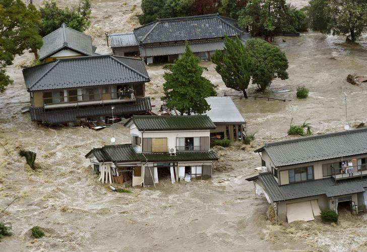 Residents are seen as they wait for rescue helicopters at a residential area flooded by the Kinugawa river, caused by typhoon Etau, in Joso, Ibaraki prefecture, Japan, in this photo taken by Kyodo September 10, 2015. One person was missing on Thursday as 90,000 people were ordered to evacuate after rivers burst their banks in cities north of Tokyo following days of heavy rain pummelling Japan, according to local media. Mandatory credit REUTERS/Kyodo ATTENTION EDITORS - FOR EDITORIAL USE ONLY. NOT FOR SALE FOR MARKETING OR ADVERTISING CAMPAIGNS. THIS IMAGE HAS BEEN SUPPLIED BY A THIRD PARTY. IT IS DISTRIBUTED, EXACTLY AS RECEIVED BY REUTERS, AS A SERVICE TO CLIENTS. MANDATORY CREDIT. JAPAN OUT. NO COMMERCIAL OR EDITORIAL SALES IN JAPAN. TPX IMAGES OF THE DAY