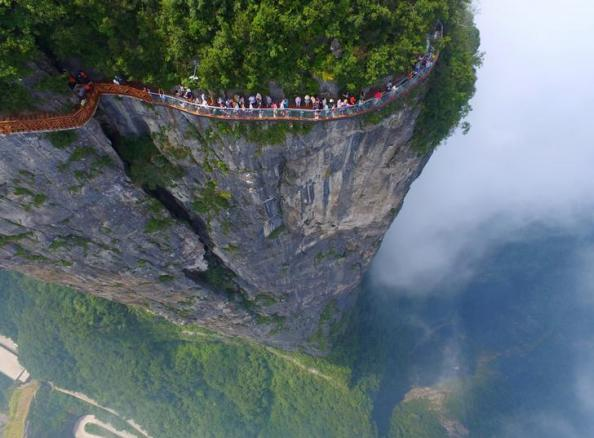 People walk on a sightseeing platform in Zhangjiajie, Hunan Province, China, August 1, 2016. REUTERS/Stringer ATTENTION EDITORS - THIS IMAGE WAS PROVIDED BY A THIRD PARTY. EDITORIAL USE ONLY. CHINA OUT. NO COMMERCIAL OR EDITORIAL SALES IN CHINA. TPX IMAGES OF THE DAY