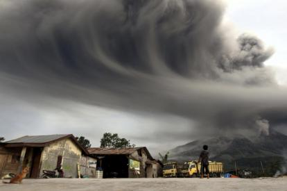 A woman looks on as Mount Sinabung spews ash, as pictured from Sibintun village in Karo district, Indonesia's north Sumatra province November 18, 2013. Mount Sinabung continued to spew volcanic ash throwing a plume 8,000 meters into the atmosphere on Monday as thousands of residents remained in temporary shelters fearful of more eruptions, according to local media. REUTERS/Roni Bintang (INDONESIA - Tags: DISASTER ENVIRONMENT TPX IMAGES OF THE DAY)