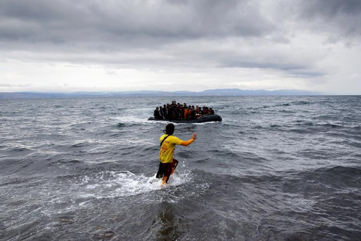 A Spanish volunteer life guard guides Afghan migrants in an overcrowded raft as they arrive at a beach during a rainstorm on the Greek island of Lesbos October 24, 2015. Over half a million refugees and migrants have arrived by sea in Greece this year and the rate of arrivals is rising, in a rush to beat the onset of freezing winter, the United Nations said. REUTERS/Yannis Behrakis