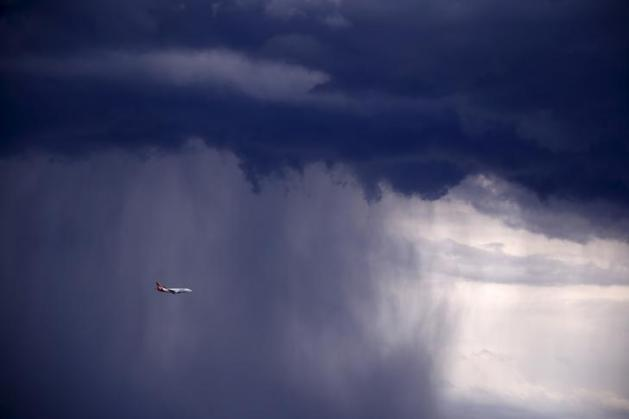 A Qantas Boeing 737-800 plane flies through heavy rain as a storm moves towards the city of Sydney, Australia, November 6, 2015. Powerful storms swept across the city on Friday, with the Australian Bureau of Meteorology issuing a warning for severe thunderstorms with large hailstones, heavy rainfall and damaging winds, local media reported. REUTERS/David Gray TPX IMAGES OF THE DAY