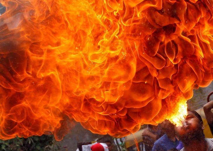 A Hindu devotee performs a stunt with fire during a rehearsal for the annual Rath Yatra, or chariot procession, which commemorates a journey by Hindu god Jagannath, his brother Balabhadra and sister Subhadra, in specially made chariots, in Ahmedabad, India, June 26, 2016. REUTERS/Amit Dave TPX IMAGES OF THE DAY