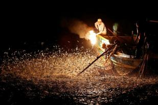 "Fishermen use a fire to attract fish on a traditional ""sulfuric fire fishing"" boat in New Taipei City, Taiwan June 19, 2016. REUTERS/Tyrone Siu SEARCH ""FIRE FISHING"" FOR THIS STORY. SEARCH ""THE WIDER IMAGE"" FOR ALL STORIES. TPX IMAGES OF THE DAY"