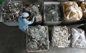"""A worker looks through industrial scrap materials at Dowa Holdings Co's Eco-System Recycling Co, a recycling plant, in Honjo, north of Tokyo March 28, 2008. Thinking of throwing out your old cell phone? Think again. Maybe you should mine it first for gold, silver, copper and a host of other metals embedded in the electronics -- many of which are enjoying near-record prices. It's called """"urban mining"""", scavenging through the scrap metal in old electronic products in search of such gems as iridium and gold, and it is a growth industry around the world as metal prices skyrocket. Picture taken March 28, 2008. To match feature JAPAN-METALS/RECYCLING. REUTERS/Yuriko Nakao (JAPAN)"""