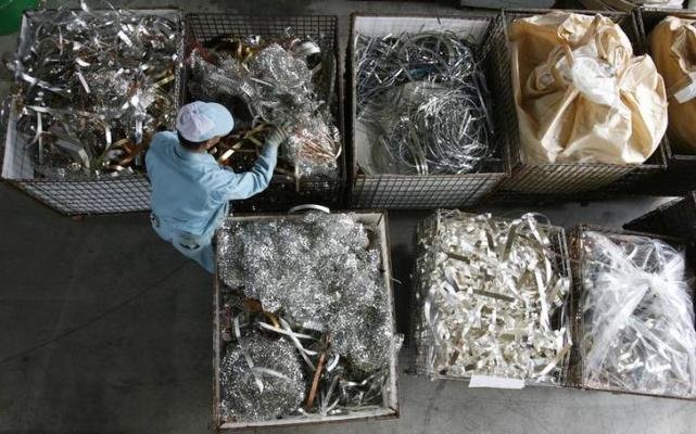 "A worker looks through industrial scrap materials at Dowa Holdings Co's Eco-System Recycling Co, a recycling plant, in Honjo, north of Tokyo March 28, 2008. Thinking of throwing out your old cell phone? Think again. Maybe you should mine it first for gold, silver, copper and a host of other metals embedded in the electronics -- many of which are enjoying near-record prices. It's called ""urban mining"", scavenging through the scrap metal in old electronic products in search of such gems as iridium and gold, and it is a growth industry around the world as metal prices skyrocket. Picture taken March 28, 2008. To match feature JAPAN-METALS/RECYCLING. REUTERS/Yuriko Nakao (JAPAN)"
