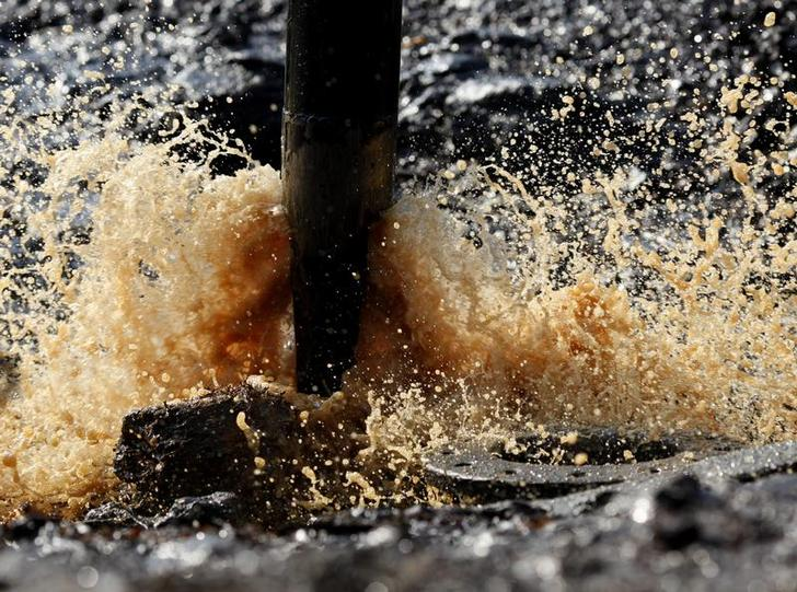 Crude oil mixed with water sprays from a well bucket in Bojonegoro, Indonesia's East Java province July 16, 2009. REUTERS/Beawiharta (INDONESIA)