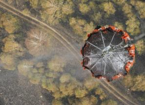 A helicopter carries water before releasing it over a forest fire near the settlement of Kustarevka in Ryazan region, some 340 km (211 miles) southeast of Moscow, August 10, 2010. Russia's deadly summer heatwave will weaken a recovery from last year's slump, economists predicted on Tuesday as wildfires raged on in several provinces and forecasters said sweltering weather won't abate this week. REUTERS/Denis Sinyakov (RUSSIA - Tags: ENVIRONMENT DISASTER IMAGES OF THE DAY)