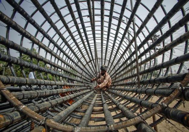 A labourer attaches iron rods to a column at the construction site of a flyover in Lahore May 26, 2011. REUTERS/Mohsin Raza (PAKISTAN - Tags: SOCIETY BUSINESS IMAGES OF THE DAY CONSTRUCTION)