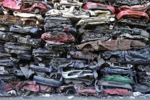 Compressed cars are seen in a recycling company in Thoerishaus near Bern July 3, 2011. Having the infrastructure in place to make it convenient for citizens to recycle, enables the Swiss to be among the top recyclers in the world. The Swiss recycle about 76 percent of everything that is recyclable. REUTERS/Ruben Sprich (SWITZERLAND - Tags: ENVIRONMENT)