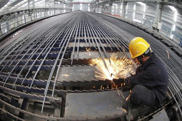 A worker cuts reinforcing bars in a steel factory in Ganyu county, Jiangsu province, February 27, 2013. Demand for iron ore in China, the world's biggest importer of the steelmaking raw material, will grow at a faster pace this year, in step with an improving economy that should boost consumption of steel, an industry official said on Wednesday. REUTERS/China Daily (CHINA - Tags: BUSINESS COMMODITIES) CHINA OUT. NO COMMERCIAL OR EDITORIAL SALES IN CHINA