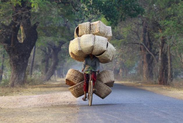 A woman cycles as she carries baskets to sell in a market near Lapdaung mountain in Sarlingyi township, March 13, 2013. REUTERS/Soe Zeya Tun (MYANMAR - Tags: SOCIETY TPX IMAGES OF THE DAY) )