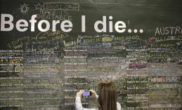 """A woman takes a picture of phrases written on a wall at a square in Sao Paulo July 3, 2014. The hoarding asks """"Before I die I want to_."""" leaving pedestrians to finish off the sentence. In a project called """"On The Sidelines"""" Reuters photographers share pictures showing their own quirky and creative view of the 2014 World Cup in Brazil. REUTERS/Nacho Doce (BRAZIL - Tags: SPORT SOCCER WORLD CUP SOCIETY)"""