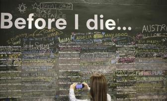 "A woman takes a picture of phrases written on a wall at a square in Sao Paulo July 3, 2014. The hoarding asks ""Before I die I want to_."" leaving pedestrians to finish off the sentence. In a project called ""On The Sidelines"" Reuters photographers share pictures showing their own quirky and creative view of the 2014 World Cup in Brazil. REUTERS/Nacho Doce (BRAZIL - Tags: SPORT SOCCER WORLD CUP SOCIETY)"
