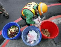 A garbage collector in Taipei separates bones from recyclable kitchen waste April 1, 2005. Starting this day, residents in 10 Taiwan cities and counties have to separate their litter into recyclables, kitchen scraps and non-recyclable waste or risk fines of up to T$6,000 ($190). The new policy is part of a government drive to cut down on garbage as the island is rapidly running out of space to dump trash. Picture taken April 1, 2005. REUTERS/Richard Chung TW/YH