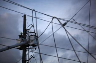 A worker of Puerto Rico's Electric Power Authority (PREPA) repairs part of the electrical grid after Hurricane Maria hit the area in September, in Manati, Puerto Rico October 30, 2017. REUTERS/Alvin Baez
