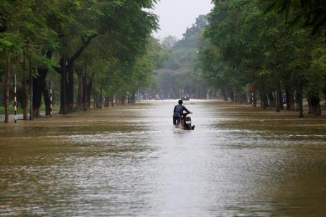A man pushes his motorcycle along flooded road after typhoon Damrey hits Vietnam in Hue city, Vietnam November 5, 2017. REUTERS/Kham