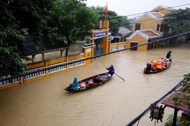 People ride a boat along submerged houses in UNESCO heritage ancient town of Hoi An after typhoon Damrey hits Vietnam November 6, 2017. REUTERS/Kham