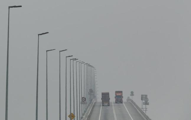 """Lorries cross a bridge shrouded in haze in Klang, Malaysia, October 7, 2015. The thick so-called """"haze,"""" caused by slash-and-burn clearances on the islands of Sumatra and Borneo, has pushed air quality to unhealthy levels in Malaysia and neighboring Singapore. REUTERS/Olivia Harris TPX IMAGES OF THE DAY"""