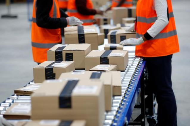 Employees sort packages at the Amazon distribution center warehouse in Saran, near Orleans, France, November 22, 2016. REUTERS/Philippe Wojazer