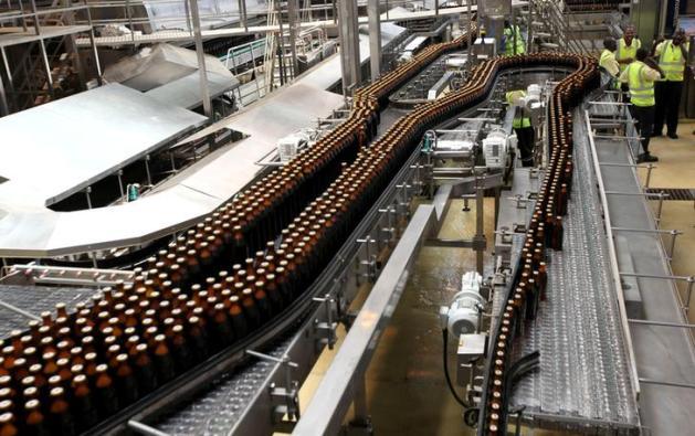 Beer bottles roll on a conveyor belt at the East African Breweries Ruaraka factory in Kenya's capital Nairobi, February 17, 2010. REUTERS/Thomas Mukoya/File Photo