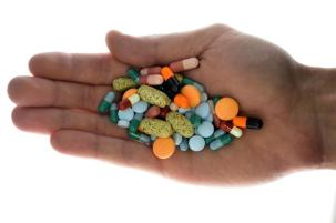 A person holds pharmaceutical tablets and capsules in this picture illustration taken in Ljubljana September 18, 2013. Picture taken September 18. REUTERS/Srdjan Zivulovic (SLOVENIA - Tags: HEALTH)