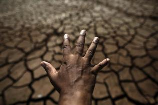 The hand of a man is seen in front of the cracked ground of Jaguary dam during a long drought period that hit the state of Sao Paulo in Braganca Paulista, 100 km from Sao Paulo January 31, 2014. This has been the hottest January on record in parts of Brazil, and the heat plus a severe drought has fanned fears of water shortages, crop damage, and higher electricity bills that could drag down the economy during an election year for President Dilma Rousseff. REUTERS/Nacho Doce (BRAZIL - Tags: POLITICS ENERGY ENVIRONMENT)