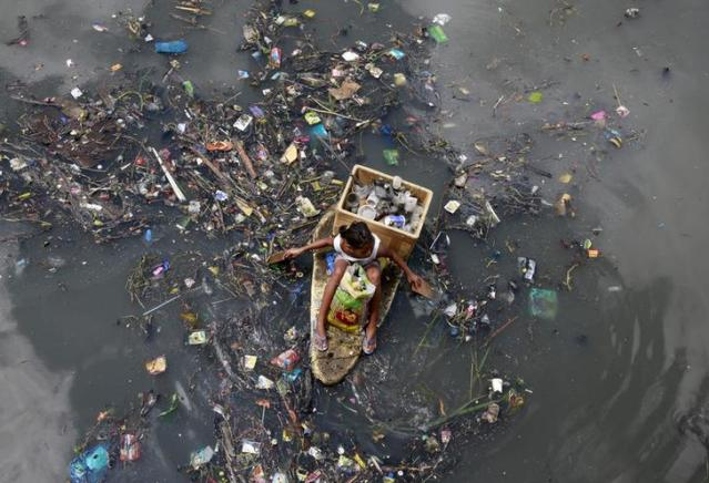 A girl sits on a makeshift styrofoam raft as she collects recyclable material from floating garbage in a polluted river at Navotas city, north of Manila, July 2, 2015. REUTERS/Romeo Ranoco
