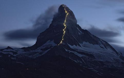 Solar powered lights are pictured along the Hoernli ridge on the Matterhorn in Zermatt, Switzerland, July 13, 2015. Zermatt celebrates the first ascent of the Matterhorn on the Hoernli ridge made by Briton Edward Whymper on July 14, 1865, with 6 other roped team members. The red light (4th from top) marks where on their descent four men fell to their death on the North face. All mountaineering activities will be banned on July 14 on the Swiss and Italian side of the Alpine summit in remembrance of the more the 500 people who died trying its summit. REUTERS/Denis Balibouse TPX IMAGES OF THE DAY