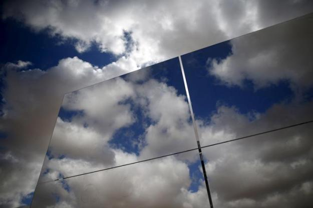 Heliostat mirrors reflect the sky in a field at the construction site of a 240 meter (787 feet) solar-power tower in Israel's southern Negev Desert, February 8, 2016. The world's tallest solar-power tower is being built off a highway in the Negev Desert in southern Israel, its backers hoping the technology will gain a foothold in the solar market even if it remains a small player for now. Picture taken February 8, 2016. REUTERS/Amir Cohen