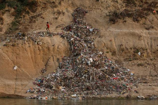 """A boy runs past a pile of garbage along the river Ganges in Mirzapur, India, April 19, 2017. REUTERS/Danish Siddiqui SEARCH """"SIDDIQUI GANGES"""" FOR THIS STORY. SEARCH """"WIDER IMAGE"""" FOR ALL STORIES."""