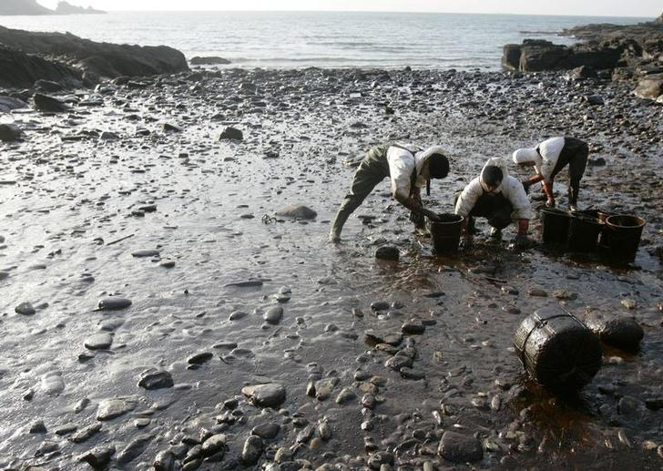 Soldiers remove crude oil, spilled from oil tanker Hebei Spirit, on a beach in Taean, about 150 km (93 miles) southwest of Seoul December 17, 2007. Thousands of soldiers and citizens have been working to remove 10,500 tonnes of oil from the Hebei Spirit after a crane mounted on a barge punched holes in its hull on December 7. REUTERS/Lee Jae-Won (SOUTH KOREA)