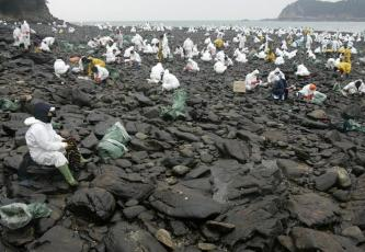 Volunteers, residents and soldiers remove crude oil spilled from oil tanker Hebei Spirit, on a beach in Taean, about 150 km (93 miles) southwest of Seoul December 17, 2007. Thousands of soldiers and citizens have been working to remove 10,500 tonnes of oil from the Hebei Spirit after a crane mounted on a barge punched holes in its hull on December 7. REUTERS/Lee Jae-Won (SOUTH KOREA)