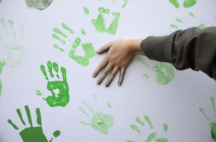 A demonstrator press her painted hand onto a board during a protest organised by the Coalicion Clima against climate change at the Reina Sofia square in Madrid December 12, 2009. REUTERS/Vincent West (SPAIN - Tags: ENVIRONMENT CIVIL UNREST IMAGES OF THE DAY)