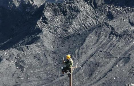 A worker sets up an electric grid at the Coc 6 open-cast coal mine in Cam Pha town, in Vietnam's northeast Quang Ninh province, 200 km (124 miles) from Hanoi September 20, 2010. Vietnam will need to import 3 million to 15 million tonnes of coal a year by 2015, rising to 21 million to 40 million annually by 2020, as new coal-fired power plants are built, Tran Xuan Hoa, chief executive of state mining firm Vinacomin said. Meanwhile, the Southeast Asian country, which is the world's top anthracite exporter, will gradually cut coal exports to 3-5 million tonnes per year, predominantly for metallurgy, a trade ministry official said. REUTERS/Kham (VIETNAM - Tags: ENERGY BUSINESS)
